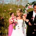 Bride and groom are showered with rose petals from their guests following the wedding ceremony.