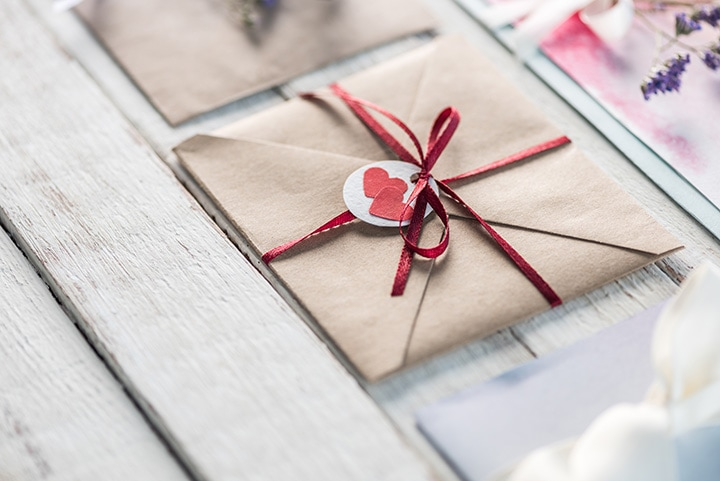 Natural, leaf-embedded wedding invitations and envelopes with vellum enclosures.