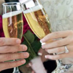 Newly married couple shares a glass of champagne at the wedding reception.