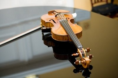 Violin rests atop the grand piano before the wedding ceremony beings.