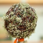 Baby's Breath wrapped around a round bridal bouquet of vine strands.