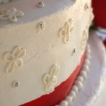White wedding cake with red stripe, floral design silver touches.