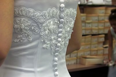 Bride shops for shoes to match her white satin and lace wedding gown.