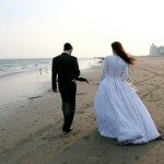 Newly married couple walks along the shoreline on a cool day.