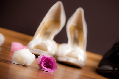 Ivory satin bridal shoes accompanied by white and pink roses.