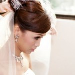 Bride gets the final touches added to her wedding day hairstyle, including the veil.