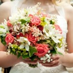 Bride carries a pink, green and white floral bouquet after the wedding ceremony.