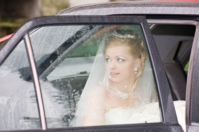 A bride looks out at her ceremony venue as she arrives by car on her wedding day.