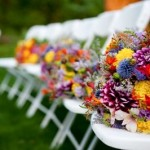 Colorful wildflower bouquets line the bridesmaids' chairs at an outdoor wedding ceremony.
