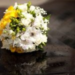 Bride's yellow, white and green bouquet atop the limousine.