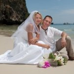 Happy couple poses for the camera on a remote island getaway.