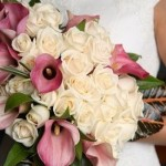 Bride carries her bouquet of ivory roses and light mauve calla lilies.