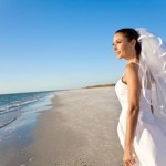 Beautiful bride looks out across the ocean after her wedding ceremony.