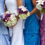 Bride poses with her bridesmaids in complementary dress shades.