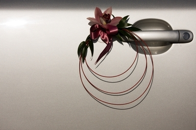 Decorative, modern floral bouquet adorns a wedding limousine.